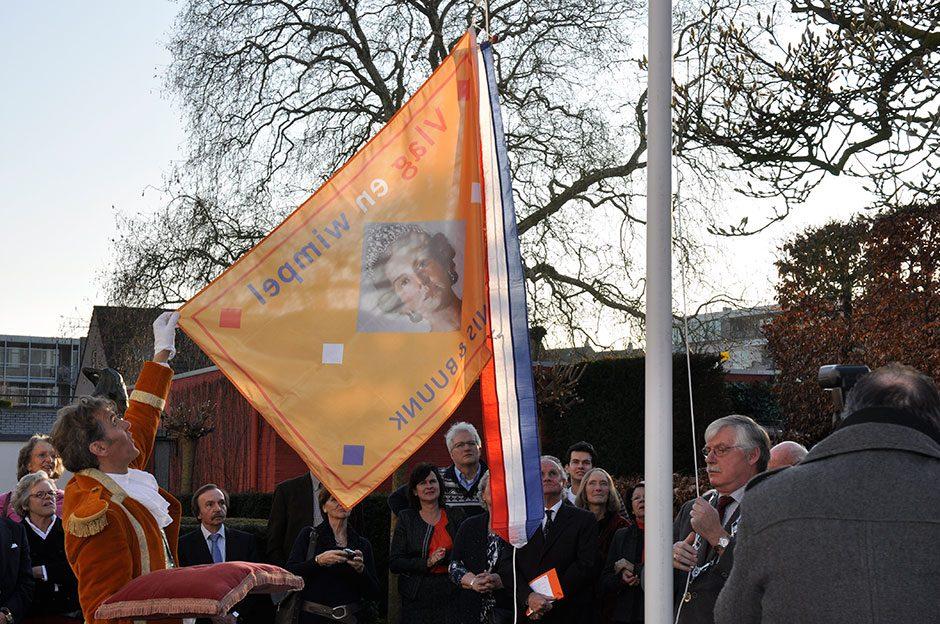 Lakei Davide Pardieu helpt burgemeester Van der Knaap met het hijsen van een speciaal ontworpen Vlag en wimpel.